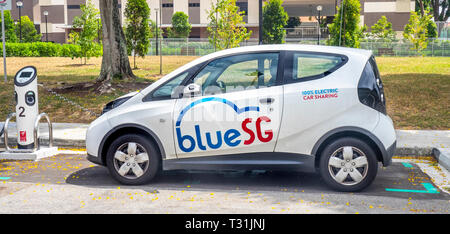 Blue SG Bolloré Bluecar, electric car charging at an electric vehicle recharching station in Singapore. - Stock Photo