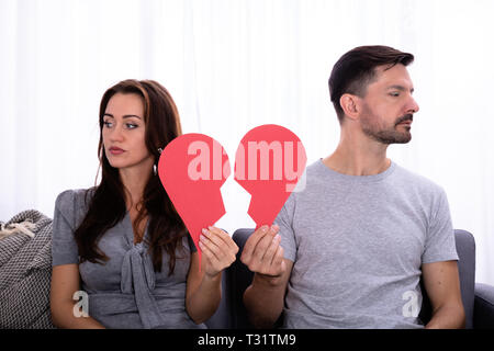 Couple Sitting On Sofa Ignoring Each Other And Holding Broken Red Heart - Stock Photo
