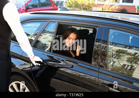Close-up Of Man's Hand Opening Car Door While Smiling Young Woman Sitting In Car - Stock Photo