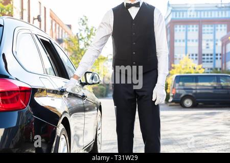 Valet's Hand Opening Black Car Door On Street - Stock Photo