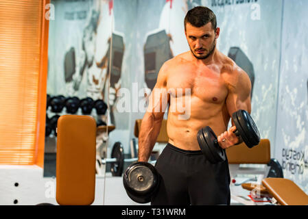 Male athlete doing biceps exercise with dumbbells - Stock Photo