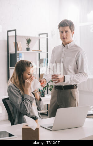 sad businessman holding pills and glass of water near blonde sneezing colleague in office - Stock Photo