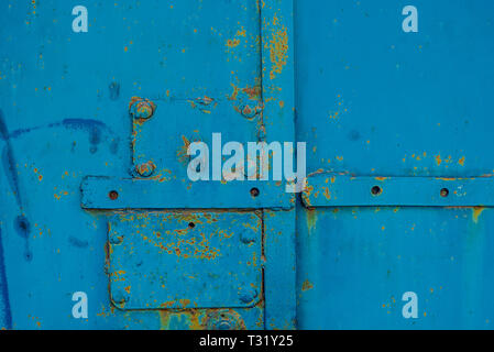 Rusty elements of lock welded by welding on steel painted old blue with rusty elements under it. Horizontal texture - Stock Photo