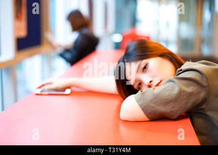Lonely sad girl looking at nowwhere on lying on the table - Stock Photo