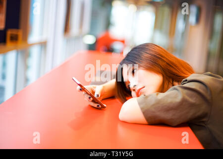 Lonely sad girl waiting for text message from smartphone lying on the table - Stock Photo