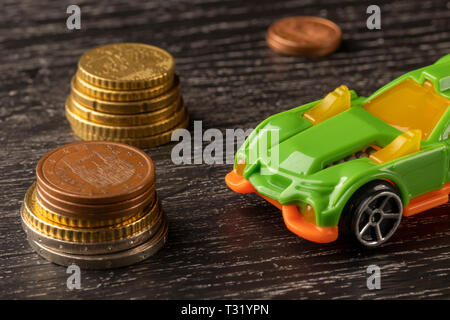 Car toy and euro coins on a dark wooden background. The concept of the financial costs of buying or renting a vehicle - Stock Photo