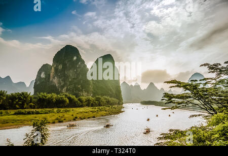 Boats on Li River in Yangshuo China surrounded by Karst Mountains - Stock Photo