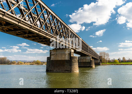 Steel, lattice structure of a railway bridge over a river with a background of blue sky with white clouds in western Germany. - Stock Photo