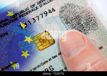 PHOTOMONTAGE, finger on German identity card with EU flag, data chip and fingerprint, FOTOMONTAGE, Finger auf deutschem Personalausweis mit EU-Fahne,  - Stock Photo