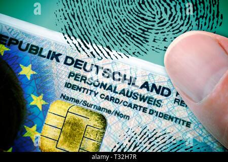 PHOTOMONTAGE, finger on German identity card with EU flag, data chip and fingerprint, FOTOMONTAGE, Finger auf deutschem Personalausweis mit EU-Fahne,  - Stock Photo