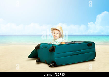 Baby girl sitting in suitcase on the sand of the beach with sea background. - Stock Photo