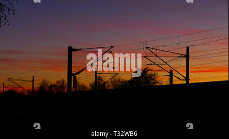 Bahngleise, Oberleitungen, Silhouette mit Bäumen, im Sonnenuntergang - Stock Photo