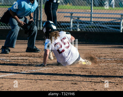 Athletic female softball player sliding safely into home plate under the legs of opponent. - Stock Photo