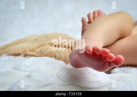 A cropped Close up of a newborn baby's toes and feet in white and neutral colored enviornment - Stock Photo