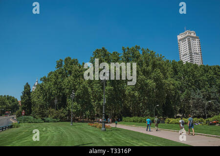 People walking towards verdant grove on the Spain Square, in a sunny day at Madrid. Capital of Spain with vibrant and intense cultural life. - Stock Photo