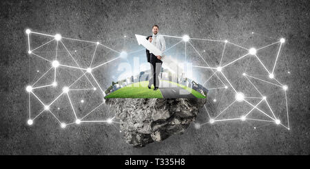 Ambitious and young businessman in suit holding huge white arrow in hands and pointing away while standing on flying island against dark gray wall on  - Stock Photo