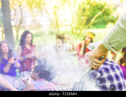 Group of people having a barbecue and drinking red wine in a park - Close up of male hand grilling meat - Happy friends having fun with a picnic - Stock Photo