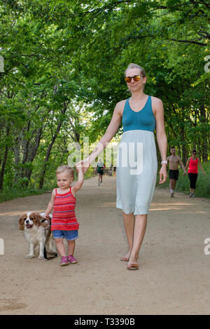 Mother, girl toddler and Cavalier King Charles Spaniel, at Butler Trail in Zilker Park in Austin, Texas, USA - Stock Photo