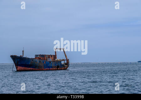 Old rusting abandoned ship with oyster farm buoys in the background off coast of Swakopmund Namibia - Stock Photo
