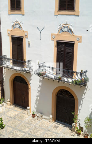 Typical Sicilian palazzo courtyard and ornate architecture with cast iron balcony and old stone paving in the city of Palermo, Sicily, Italy - Stock Photo
