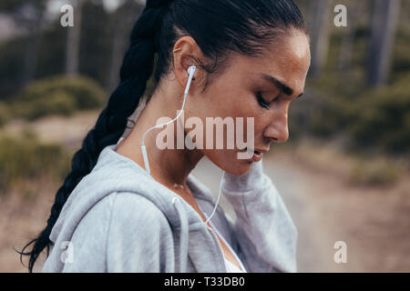 Side view of a female athlete wearing earphones listening to music. Sportswoman listening to music outdoors in morning. - Stock Photo