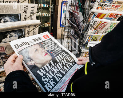 Paris, France - 29 Mar 2019: Newspaper stand kiosk selling press with senior male hand buying latest Daily Mail UK press featuring Theresa may PM on front cover  - Stock Photo