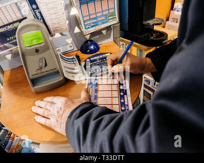 Paris, France - 29 Mar 2019: Senior man marking numbers on Euromillions ticket inside tabac press kiosk hoping to win the big jackpot of 10000000 millions euros  - Stock Photo