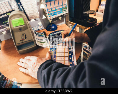 Paris, France - 29 Mar 2019: Senior male hands marking numbers on Euromillions ticket inside tabac press kiosk hoping to win the big jackpot of 10000000 millions euros  - Stock Photo