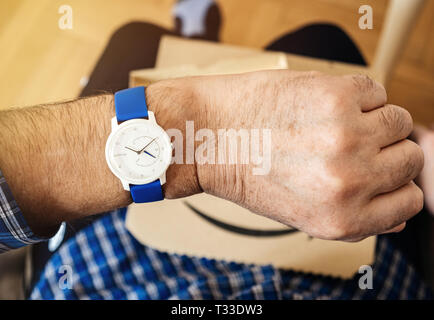 Paris, France - Mar 29, 2019: Senior man checking time on latest Withings move activity tracking watch with Unsurpassed battery life and Infinite possibilities for customize - amazon prime cardboard - Stock Photo