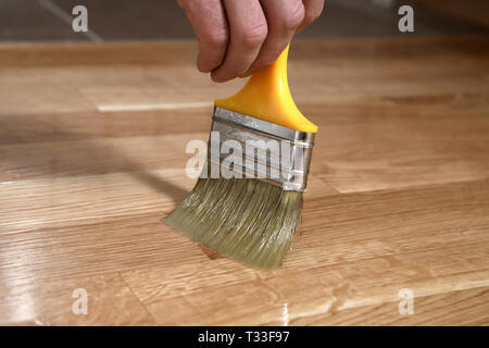 Varnishing lacquering parquet floor by paintbrush - second layer. Home renovation parquet. Varnish paintbrush strokes on a wooden parquet. Application - Stock Photo