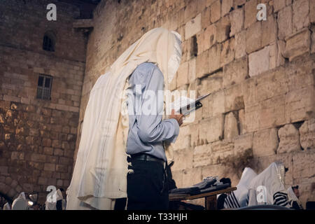Religion Jew reading prayer book. Torah on the table in front of the wailing wall in the old city of Jerusalem Israel. - Stock Photo