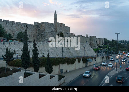 Panorama of David's Tower in old city of Jerusalem, Israel. Jerusalem old city wall with the view of the tower at skyline background and city road bus - Stock Photo