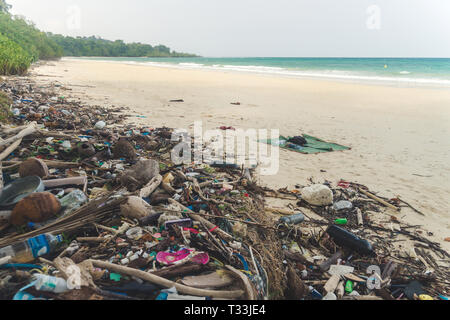 Beach pollution. Plastic bottles and other trash on sea beach. garbage nailed by a wave from the sea on a beach - Stock Photo