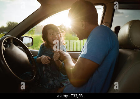 father daughter playing in the car together - Stock Photo
