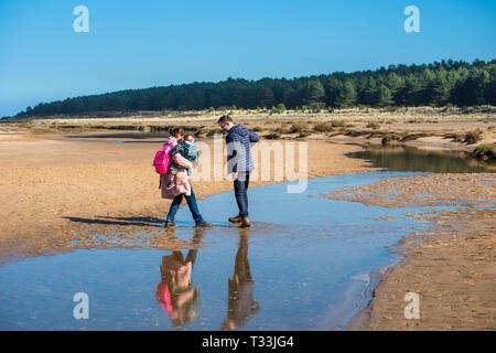 A family cross water pools left by the tide on sandy beach at Holkham bay, North Norfolk coast, East Anglia, England, UK. - Stock Photo