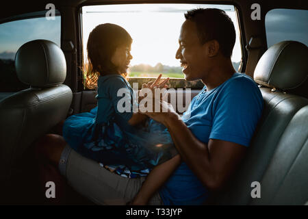 asian daughter with father in the car playing - Stock Photo