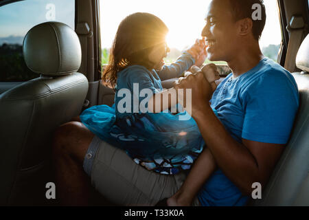 daddy tickling her little girl in the car - Stock Photo