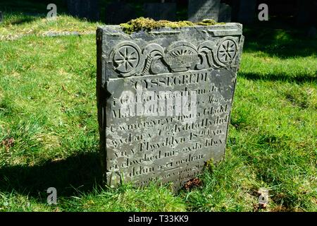 Old gravestone tombstone with Welsh inscription in the circular graveyard of St Johns Church Ysbyty Cynfyn Devils Bridge Wales Cymru UK - Stock Photo