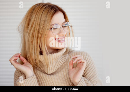 Stylish and beautiful young blonde in beige oversize sweater. Young woman with glasses, portrait - Stock Photo