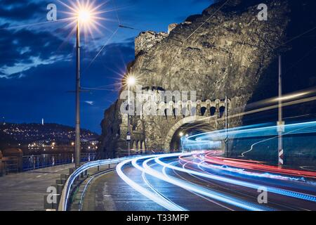 Night traffic in city. Light trails of tram and cars on road to Vysehrad tunnel.  Prague, Czech Republic