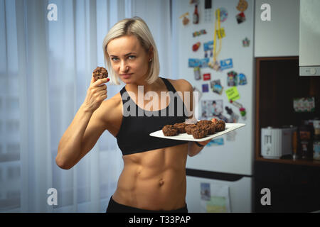 Young caucasian woman with abdominal muscle with healthy muffins. Healthy nutrition concept. - Stock Photo