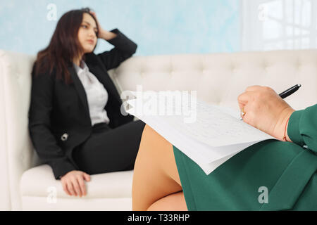 Blurred of young woman sitting on sofa talking to his therapist at therapy session, selective focus on the psychologist - Stock Photo