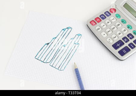 The handmade drawing of a graphic on the squared sheet, on the desk the calculator and the pen - Stock Photo