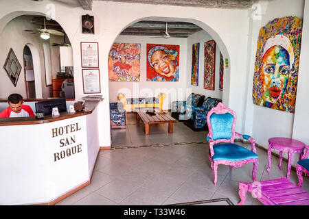 Cartagena Colombia Old Walled City Center centre Getsemani Hotel San Roque hotel inside lobby front desk reservation man clerk colorful decor painting - Stock Photo
