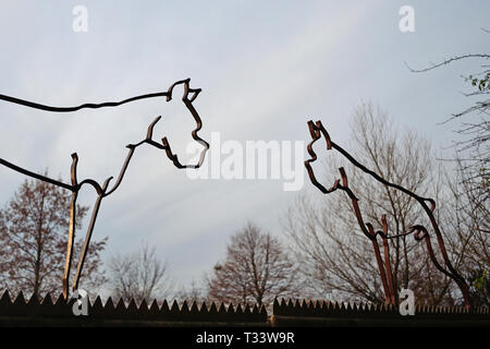 Outdated iron silhouette sculptures in the shape of German Boxer dogs with cropped ears and tails, a practice prohibited in Germany in modern days - Stock Photo