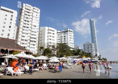 Cartagena Colombia El Laguito high rise apartment condominium buildings Caribbean Sea Lagito Beach waterfront Hispanic resident residents umbrellas ve - Stock Photo