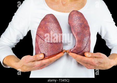 Woman holds models of two lungs at white body isolated on black background - Stock Photo