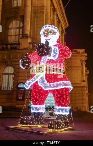 Zagreb, Croatia - 31th December, 2018 : A large illuminated Santa Claus in front of the Croatian National Theater building at Advent time. - Stock Photo