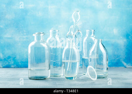 Group of glass jars and bottles with clear water on blue background - Stock Photo