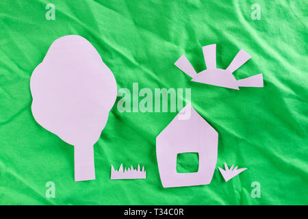 House on green field made from paper - Stock Photo
